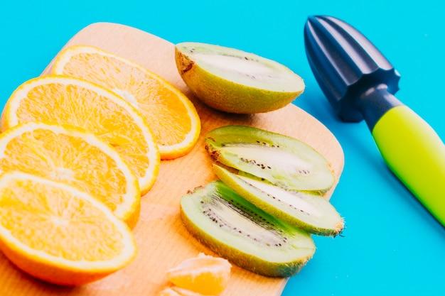 Scheiben von orangen und kiwischeiben und hand juicer auf blauem hintergrund