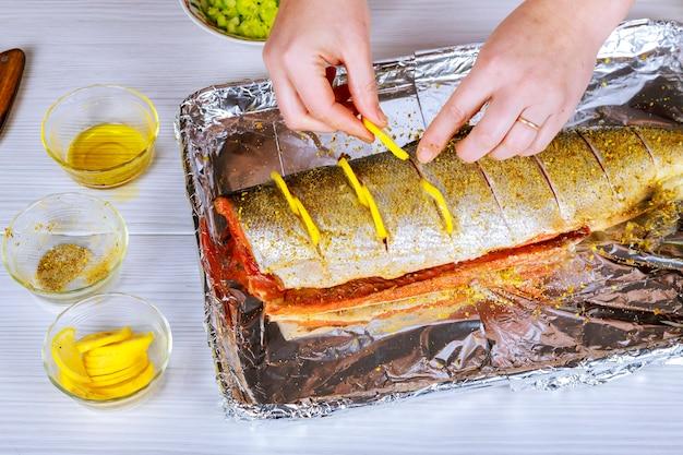 Scheiben von rohem lachs geschmiert mit gewürzen und olivenölschiefer auf einer plattennahaufnahme.