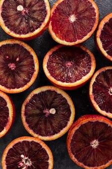 Scheiben von rotem orange auf dunkler tischoberansicht