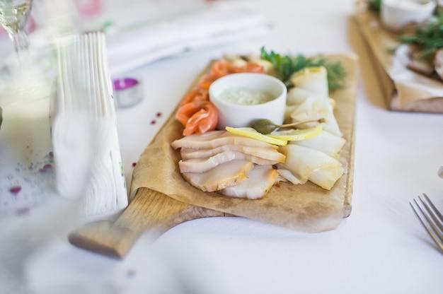 Scheiben von verschiedenem gesalzenem fisch - lachs, muksun, öliger fisch auf hölzernem schneidebrett. restaurant