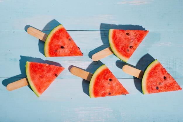 Scheiben wassermelone auf blauem schreibtisch aus holz.
