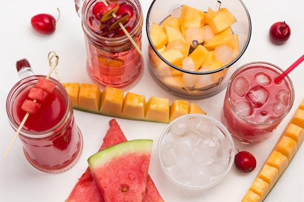 Scheiben wassermelone und melone. stücke von melone und wassermelone im mixbecher. fruchtgetränk aus apfel, melone und wassermelone im glas. eis in einer glasschale. weißer hintergrund. flach liegen