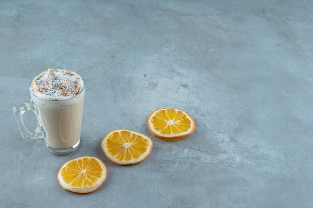 Scheiben zitrone neben einer tasse cappuccino auf blauem hintergrund.