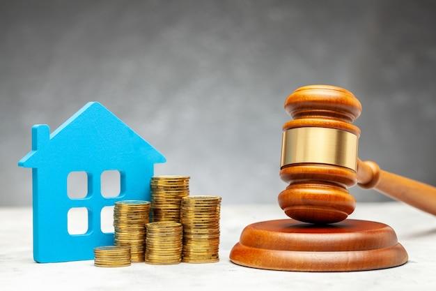 Scheidung per gesetz. aufteilung des vermögens nach einer scheidung. haus mit geld und einem richterhammer.