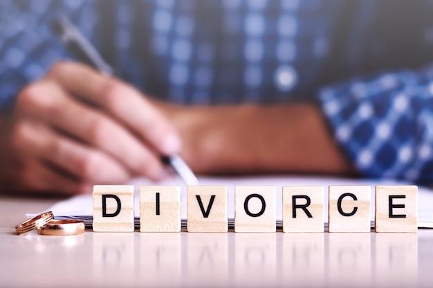 Scheidung. wort aus holzbuchstaben mit ringen und ein mann, der die vereinbarung auf dem hintergrund unterzeichnet