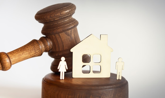 Scheidungskonzept mit hammer und holzhaus und figur auf weißem hintergrund