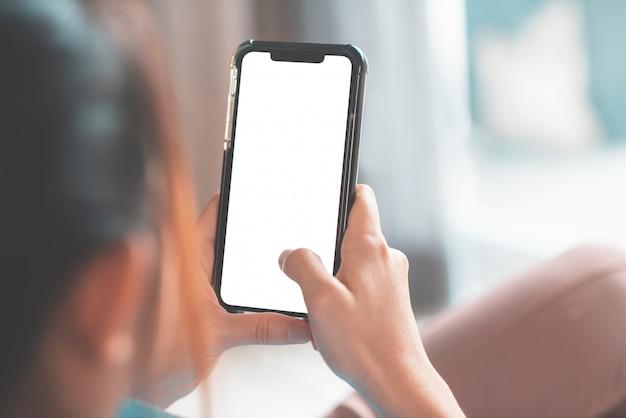 Scheinbild der hand, die smartphone mit leerem weißen bildschirm im innenraum berührt