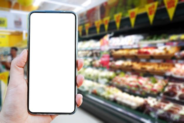 Scheinbild einer hand, die einen leeren bildschirm des smartphones auf unscharfem hintergrund hält.