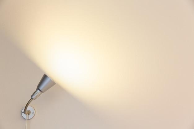 Scheinwerfer, der auf zementwandhintergrund, leerer raumwandhintergrund mit glänzendem ligh scheint