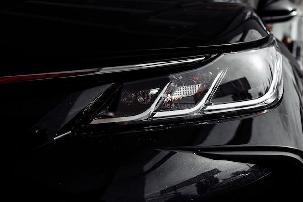 Scheinwerfer des modernen prestigeträchtigen schwarzen autos hautnah. schließen sie herauf foto des modernen autos, detail des scheinwerfers. scheinwerfer auto projektor led einer modernen luxus-technologie und auto detail. selektiver fokus