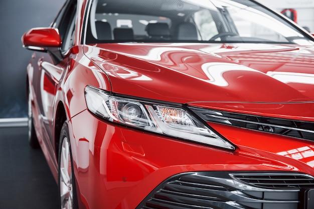 Scheinwerfer des neuen roten autos im autohaus.