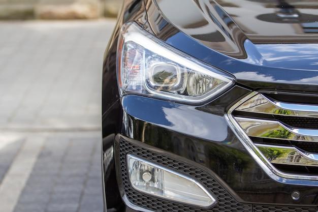 Scheinwerfer eines autos, das am straßenrand auf einem parkplatz geparkt ist.