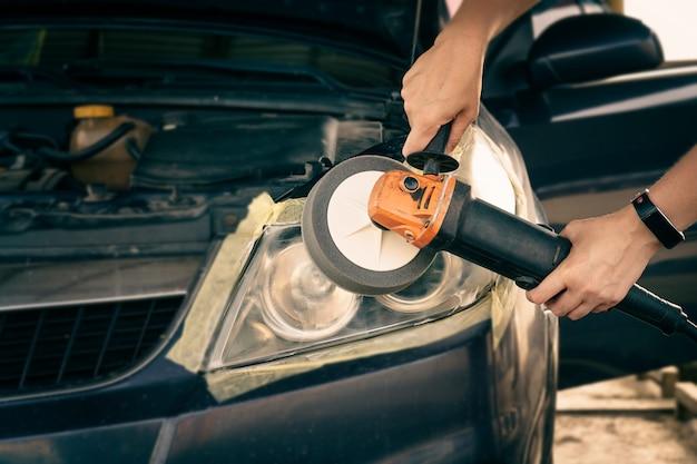 Scheinwerfer mit puffermaschine reinigen. der meister poliert die scheinwerfer des autos.