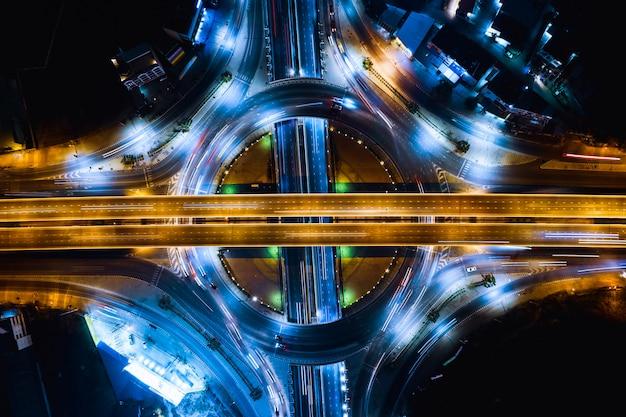 Scheinwerferauto des langen belichtungsnachtverkehrs auf dem ringstraßen- und autobahnüberführungsschnitt, der das stadttransport-logistikgeschäft in thailand anschließt