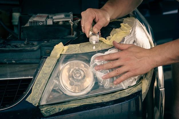 Scheinwerferreinigung. der meister trägt die paste auf die gereinigte oberfläche auf, poliert die scheinwerfer des autos.