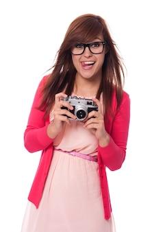 Schelmische junge frau mit vintage-kamera