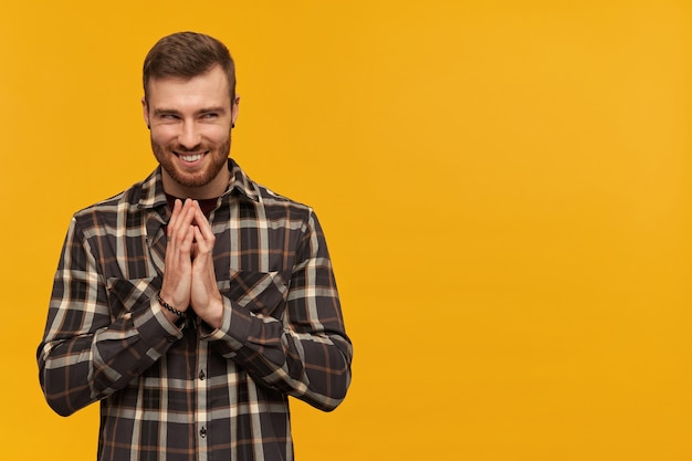 Schelmischer arroganter junger mann im karierten hemd mit bart, der hände reibt und einen bösen plan über gelber wand entwirft, der zur seite schaut