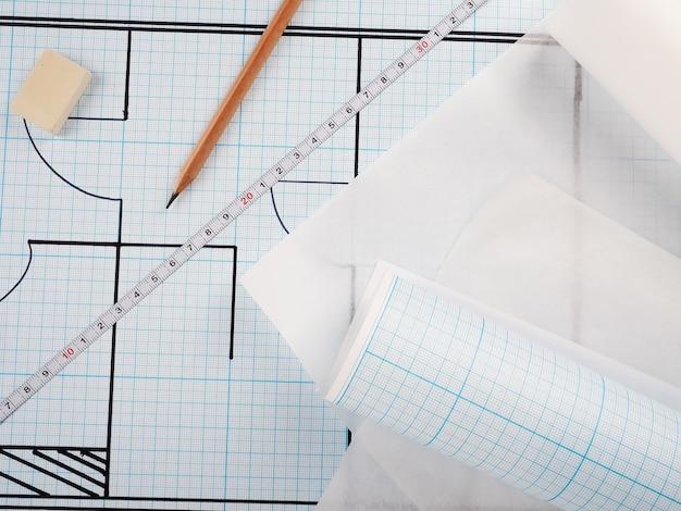 Schematische darstellung der wohnung, zeichnung auf millimeterpapier in einer rolle. builder-konzept der reparatur und des designs.