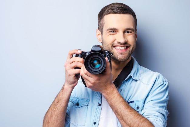 Schenk mir ein lächeln! hübscher junger mann, der digitalkamera hält und lächelt, während er vor grauem hintergrund steht
