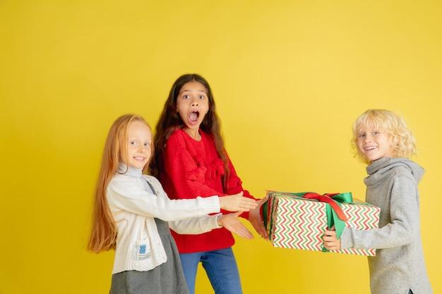 Schenken und beschenken an den weihnachtsfeiertagen. gruppe glücklicher lächelnder kinder, die spaß haben