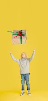 Schenken und beschenken an den weihnachtsfeiertagen. kleiner junge, der spaß hat, isoliert auf gelbem studio?