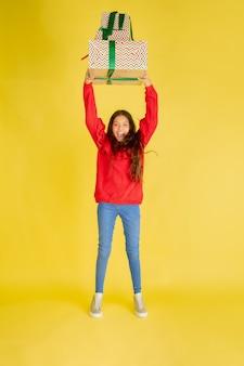 Schenken und beschenken an den weihnachtsfeiertagen. teenie-mädchen, das spaß hat, isoliert auf gelbem studio