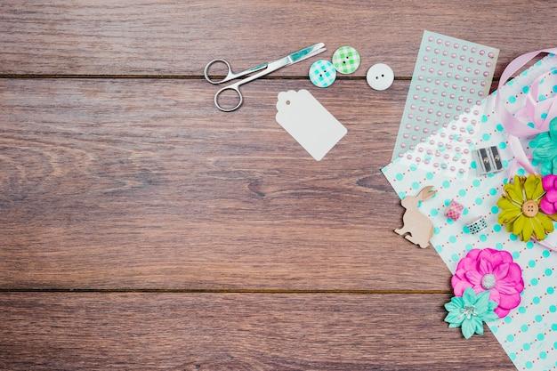 Schere; etikett; tasten; perlenaufkleber und -blumen auf papier über dem hölzernen hintergrund