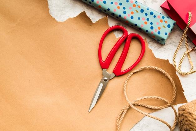Schere; juteschnur und verpackte geschenkbox über dem braunen papier