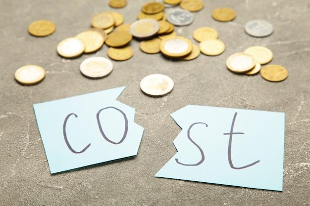 Schere schneidet das wort kostenkonzept für rezession oder kreditkrise. draufsicht