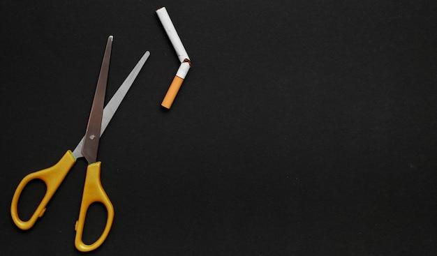 Schere und defekte zigarette auf schwarzem hintergrund