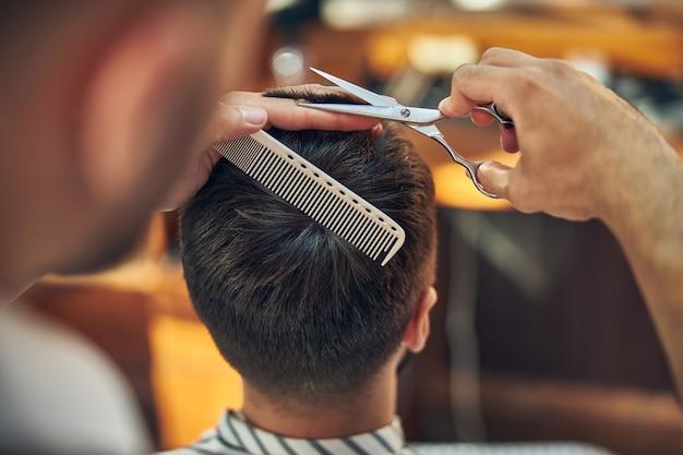 Schere und haarkamm in den händen eines professionellen friseurs, der für seinen kunden am haarschnitt arbeitet
