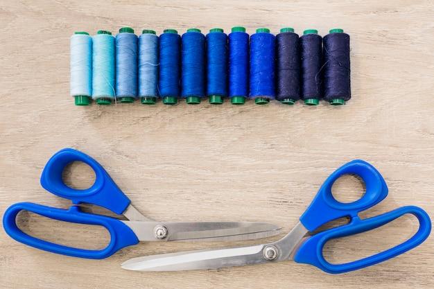 Schere und threads in einer reihe auf hölzernen hintergrund angeordnet