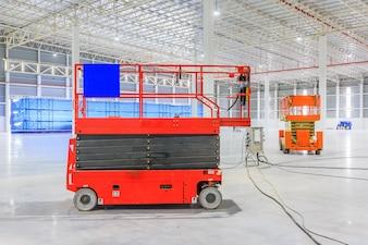 Scherenhebebühne mit Hydrauliksystem in Richtung eines Fabrikdaches angehoben