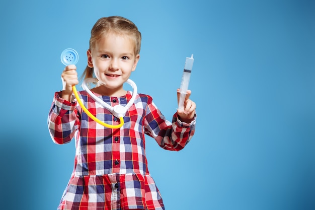 Scherzen sie das mädchen, das doktor mit spritze und stethoskop auf einem blauen hintergrund spielt.