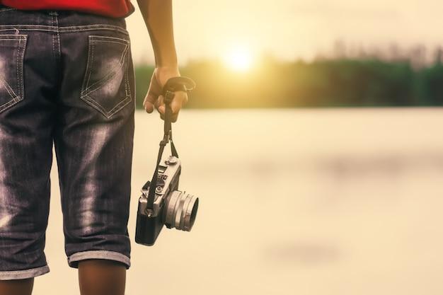 Scherzen sie den jungenphotographen, der eine weinlesekamera auf dem flussuferpark hält.