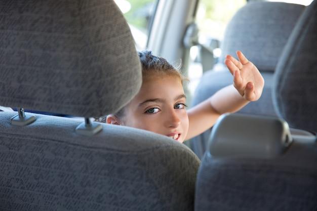 Scherzen sie glückliche grußgestenhand des mädchens im auto innen