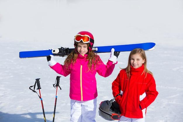 Scherzen sie mädchenschwester im winterschnee mit skiausrüstung