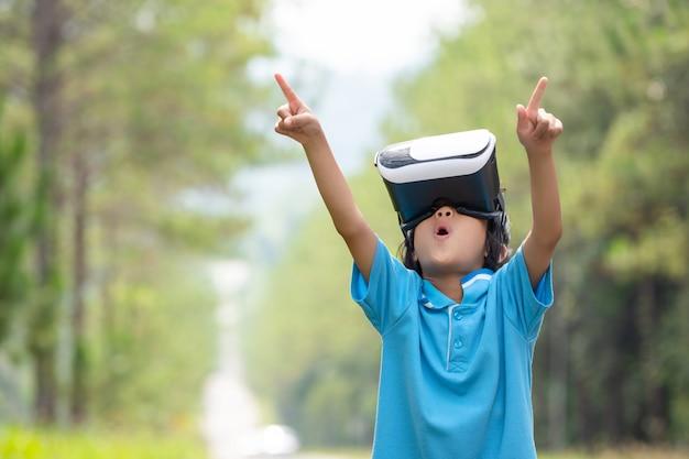 Scherzt aufregende aufpassende kastengläser der virtuellen realität auf unscharfem baum