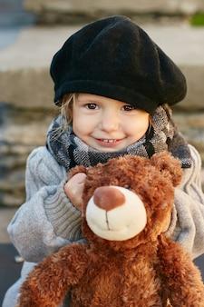 Scherzt baby in der retro- herbstfrühlingskleidung. kleines kind sitzt lächelnd in der natur, schal um den hals, kühles wetter. helle emotionen in seinem gesicht. ,