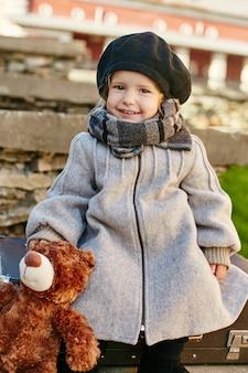 Scherzt baby in der retro- herbstfrühlingskleidung. kleines kind sitzt lächelnd in der natur
