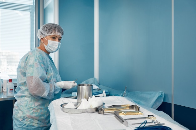 Scheuerkrankenschwester, die medizinische instrumente für die operation vorbereitet