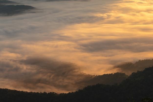 Schicht berge im nebel zur sonnenaufgangzeit