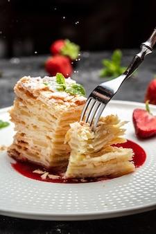 Schichtkuchen napoleon mit cremiger vanillecreme, äpfeln und erdbeermarmelade dekoriert minze, schwarzer hintergrund für menü