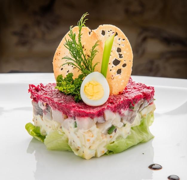 Schichtsalat mit hering, rüben, karotten, zwiebeln, kartoffeln und eiern
