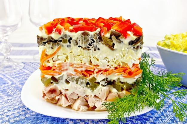 Schichtsalat mit hühnchen, ei, champignons und gurken, karotten und paprika, mayonnaise auf dem teller mit dill auf dem hintergrund der tischdecke