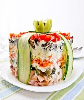Schichtsalat mit hühnchen, ei, champignons und gurken, karotten und paprika, mayonnaise auf dem teller vor dem hintergrund gestreifter servietten