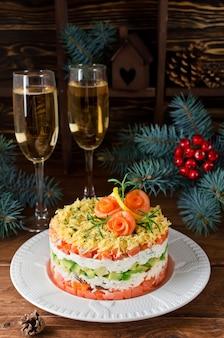 Schichtsalat mit lachs, avocado und frischkäse. salat für den feiertagstisch
