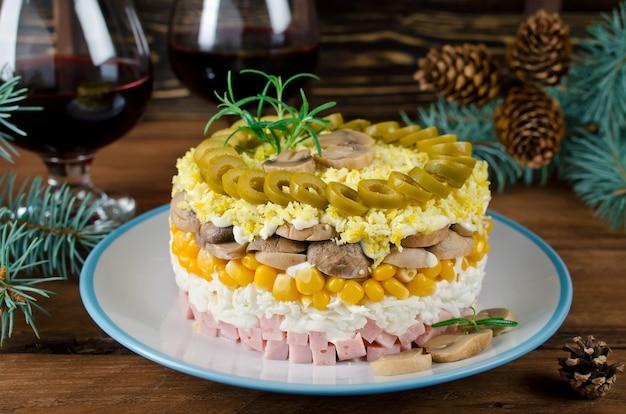Schichtsalat mit schinken, champignons und mais. salat für den feiertagstisch