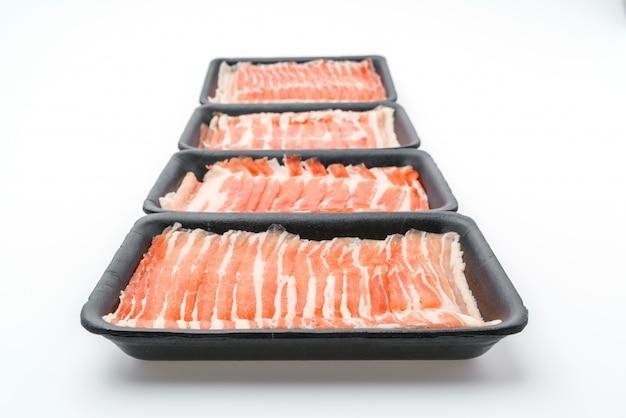 Schieben von rohem schweinefleisch auf weißem hintergrund.