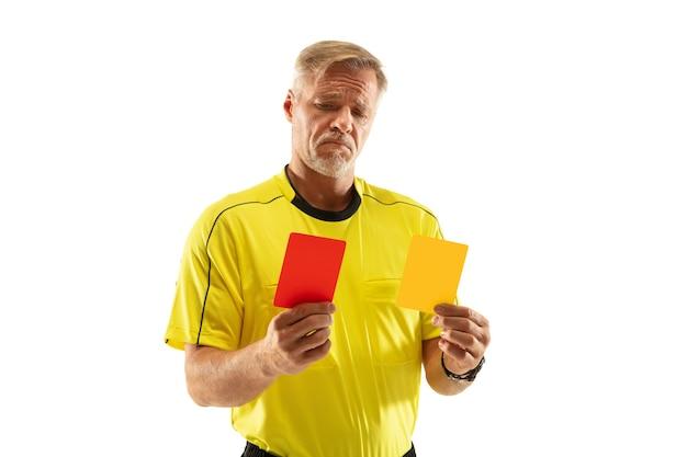 Schiedsrichter, der einem fußball- oder fußballspieler eine rote und gelbe karte zeigt, während er an der weißen wand spielt. konzept des sports, regelverletzung, kontroverse themen, überwindung von hindernissen.